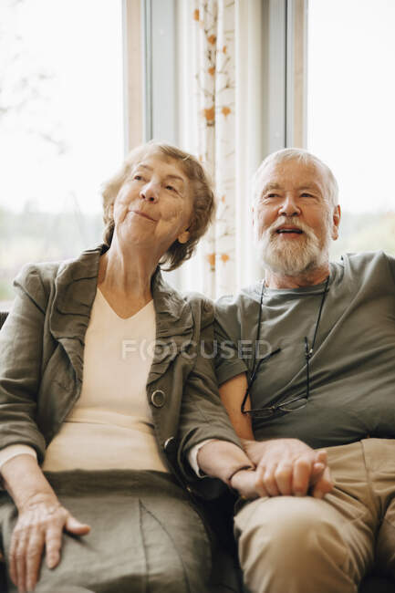 Senior couple holding hands while sitting against window at nursing home — Stock Photo