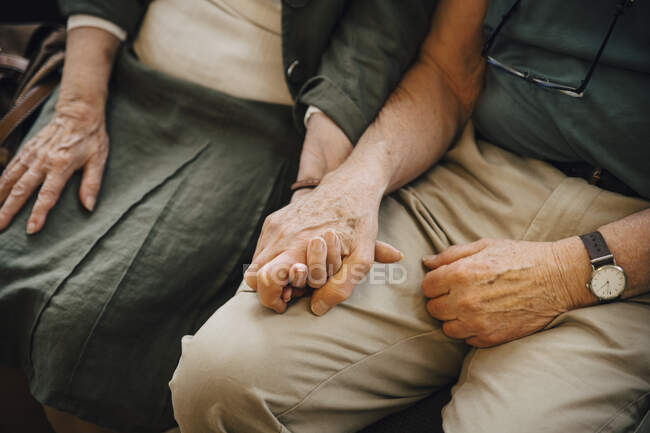 Midsection of senior couple holding hands sitting at nursing home — Stock Photo