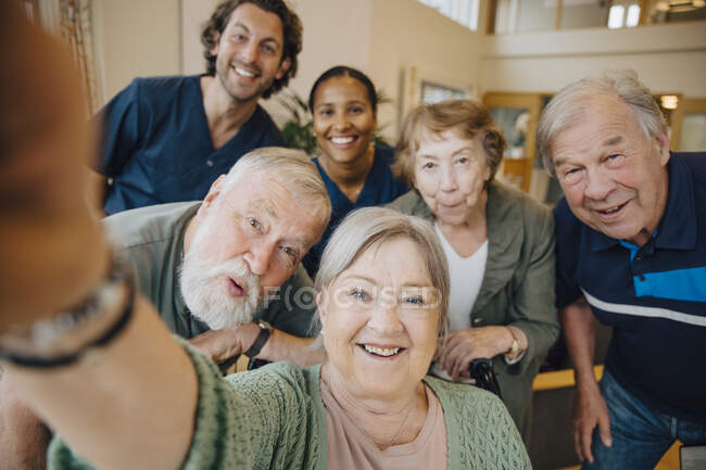 Retired elderly woman taking selfie with friends and caregivers at retirement home — Stock Photo