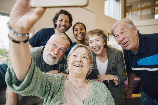 Senior woman taking selfie with friends and healthcare workers at retirement home — Stock Photo