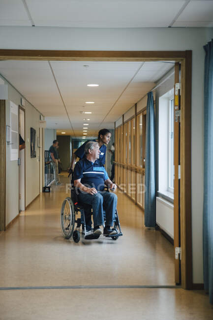 Full length of female nurse pushing disabled elderly man on wheelchair while looking away in alley at retirement home — Stock Photo