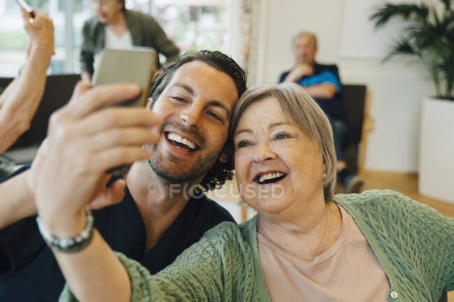 Smiling senior woman taking selfie with male healthcare worker while sitting at retirement home — Stock Photo