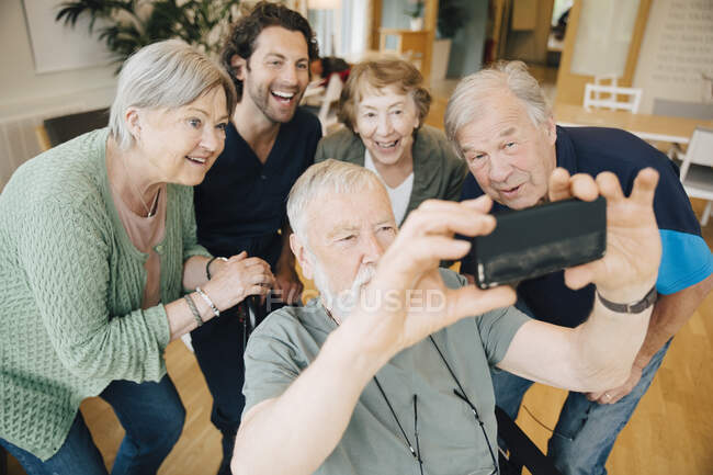 Disabled senior man taking selfie with friends and male nurse at retirement home — Stock Photo