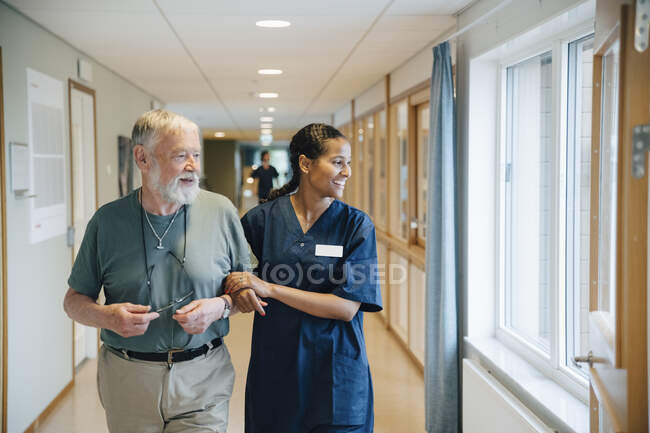 Smiling senior man walking arm in arm with female nurse while looking away in alley at nursing home. - foto de stock