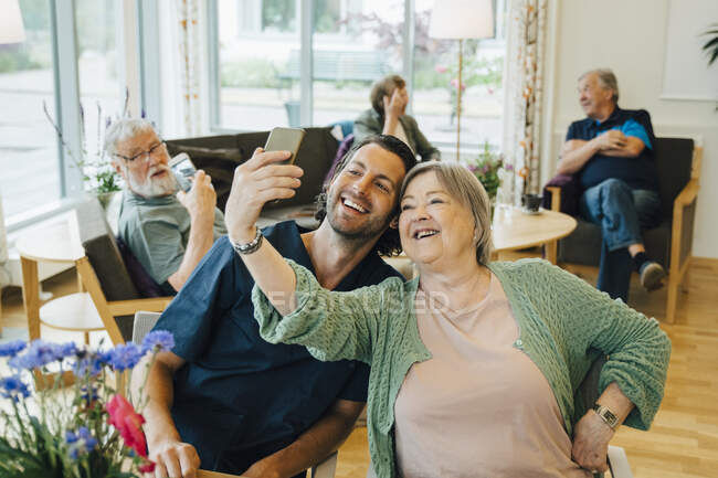 Smiling Senior woman taking selfie with male nurse while sitting at retirement home. - foto de stock