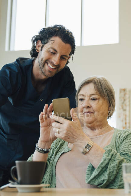 Smiling male caregiver assisting senior woman using smart phone in nursing home — Stock Photo