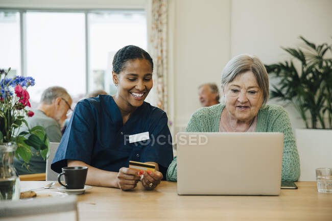 Smiling female caregiver assisting senior woman doing online shopping with credit card and laptop in nursing home — Stock Photo