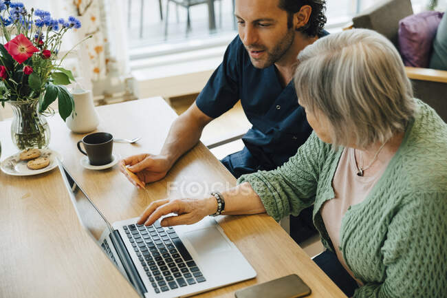 Confident male caregiver assisting senior woman doing online shopping with credit card and laptop in nursing home — Stock Photo
