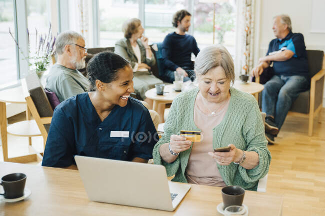 Cheerful female healthcare worker sitting by senior woman doing online shopping with credit card and smart phone in nursing home — Stock Photo