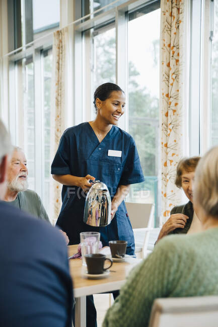 Smiling female nurse serving drink to senior women and men at dining table in nursing home — Stock Photo