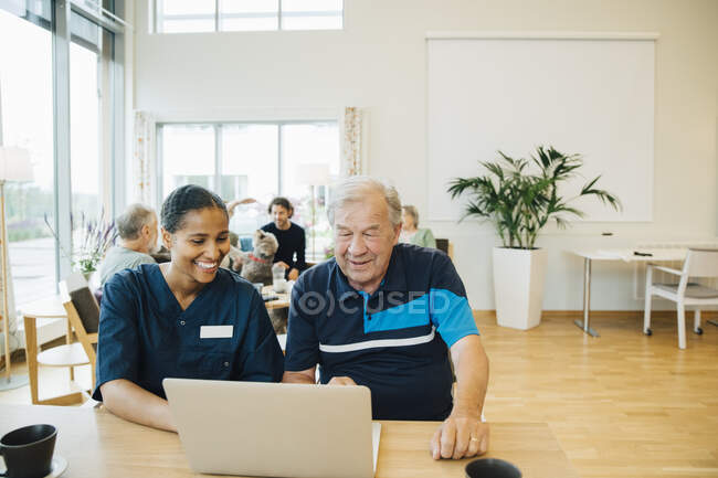 Smiling young female healthcare worker assisting senior man in using laptop at dining table — Stock Photo