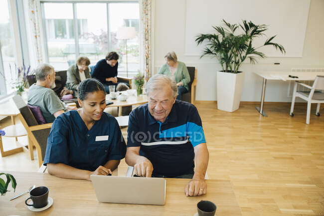 Young female nurse assisting senior man using laptop at dining table in retirement home — Stock Photo