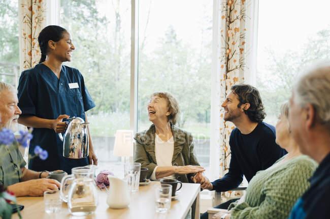 Enfermeira alegre conversando com a mulher sênior sentada com amigos e neto à mesa de jantar em casa de repouso de enfermagem — Fotografia de Stock