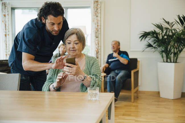 Confident male caregiver assisting senior woman using smart phone in nursing home — Stock Photo