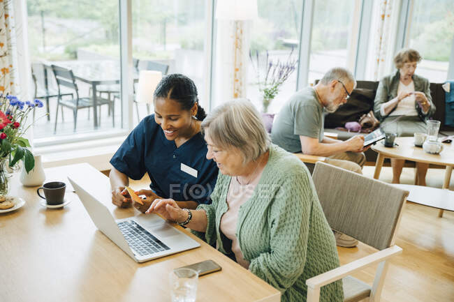 Smiling female healthcare worker assisting senior woman doing online shopping with credit card and laptop in nursing home — Stock Photo