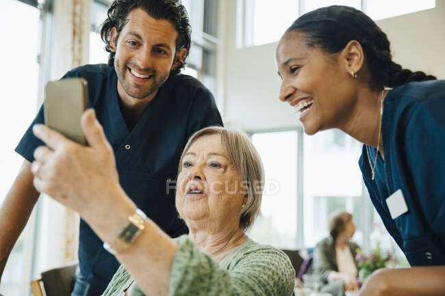 Senior woman taking selfie with smiling male and female nurses at retirement home — Stock Photo