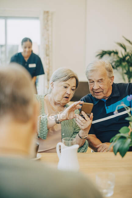 Senior woman sharing smart phone with man while sitting at dining table in retirement home — Stock Photo