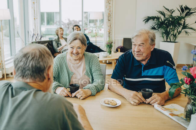 Elderly senior friends talking while sitting at dining table in nursing home — Stock Photo