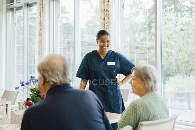Smiling young female nurse looking at senior woman sitting by man at dining table in elderly nursing home. - foto de stock