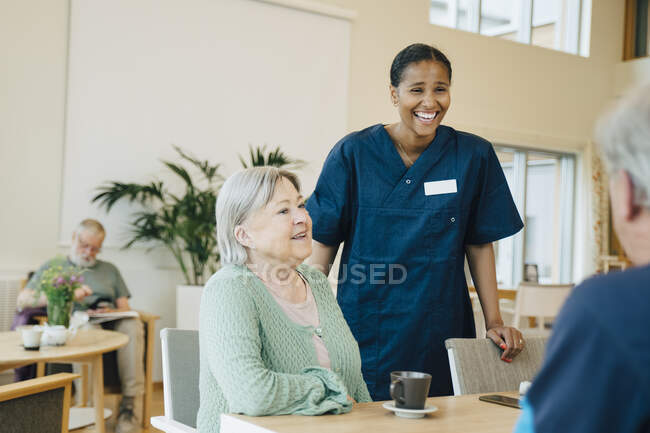 Cheerful young female nurse standing by senior woman while looking at man in retirement home — Stock Photo
