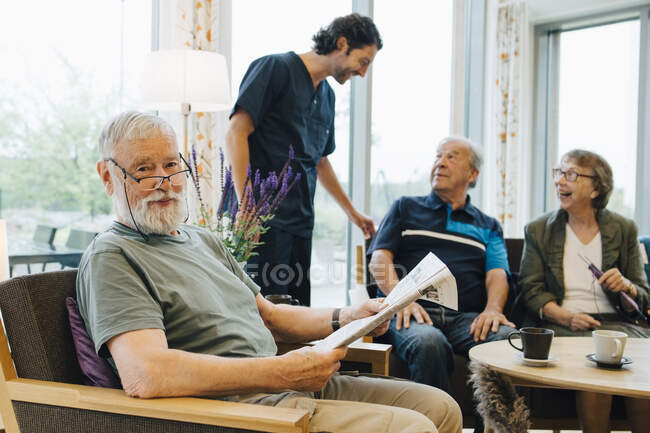 Portrait of retired senior man sitting with newspaper on armchair by friends and caretaker at elderly nursing home — Stock Photo