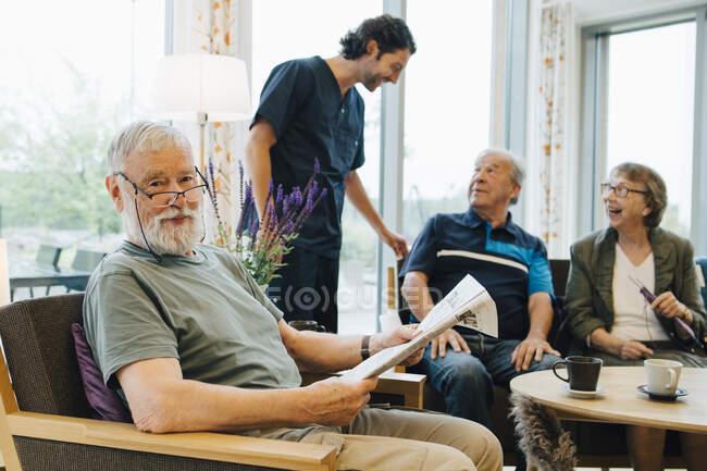 Portrait d'un retraité assis au journal sur un fauteuil par des amis et un gardien dans un foyer pour personnes âgées — Photo de stock