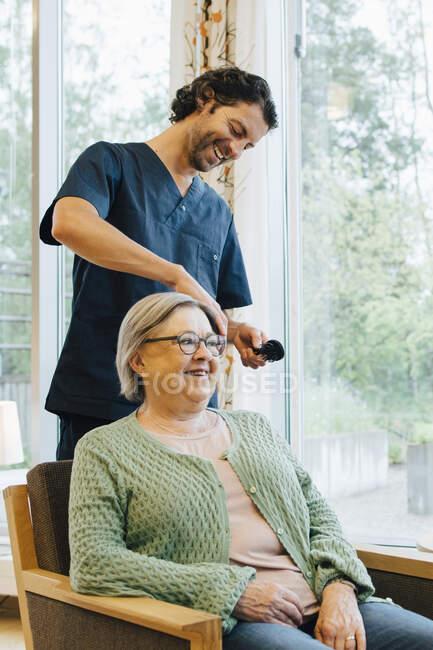 La enfermera macho sonriente cepillarse el cabello de la mujer mayor al jubilarse a casa - foto de stock