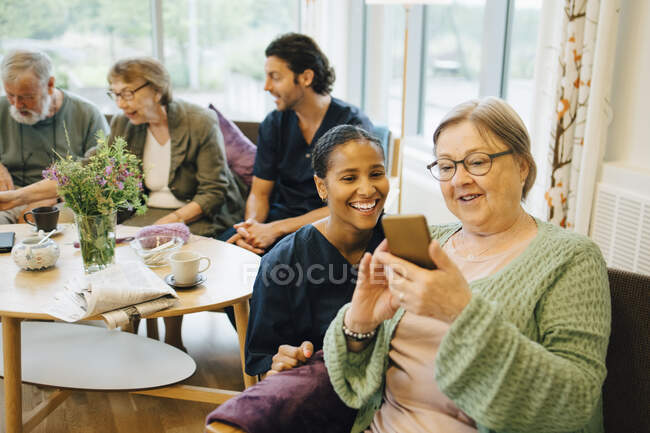 Retired elderly woman sharing smart phone with smiling young female nurse at community outreach — Stock Photo