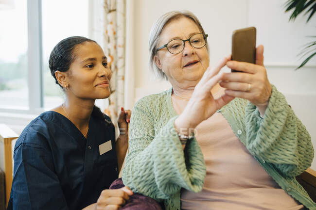 Sorrindo cuidador feminino olhando para a mulher sênior usando telefone celular em casa de repouso de enfermagem — Fotografia de Stock