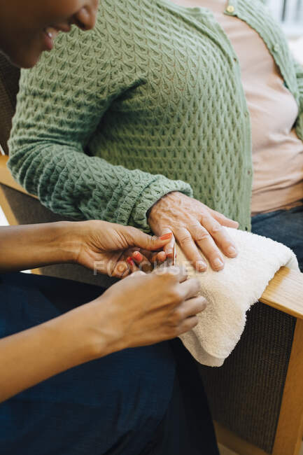 Midsection of senior women getting her nails in shape from young female caretaker at nursing home. - foto de stock