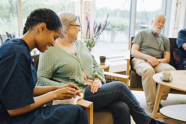 Молода жінка-доглядач кладе ніготь старшої жінки, сидячи в будинку престарілих. — стокове фото