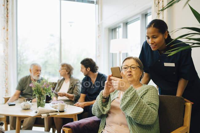 Mulher idosa aposentada compartilhando telefone inteligente com a jovem enfermeira no alcance da comunidade — Fotografia de Stock