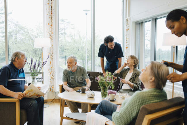 Male and female nurses taking care of elderly retired people at nursing home — Stock Photo