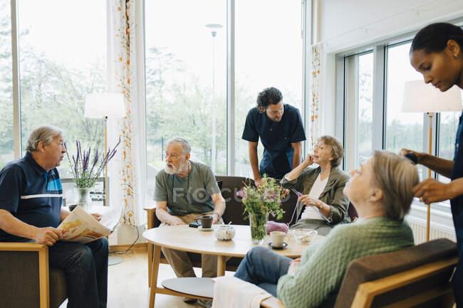Infermiere e infermiere di sesso maschile e femminile che si prendono cura di anziani pensionati a casa di cura — Foto stock