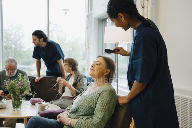 Seitenansicht einer Pflegerin streicht Seniorin im Pflegeheim die Haare — Stockfoto