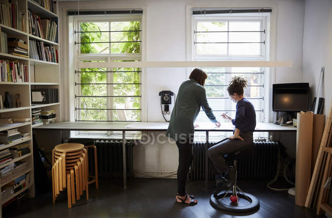 Full length of female architects discussing at table in office — Stock Photo