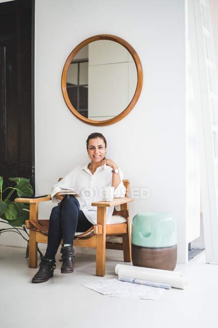 Retrato do profissional de design feminino sentado na cadeira em casa escritório — Fotografia de Stock