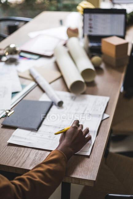 Gestutzte Hand einer Designerin, die am heimischen Schreibtisch an einem Entwurf arbeitet — Stockfoto