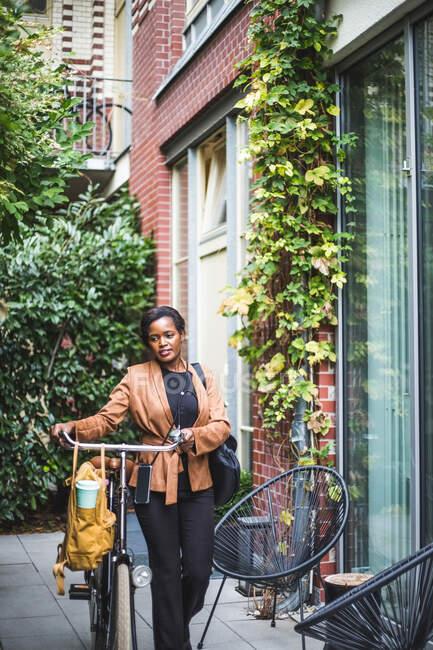 Architecte femme marche avec vélo par maison — Photo de stock