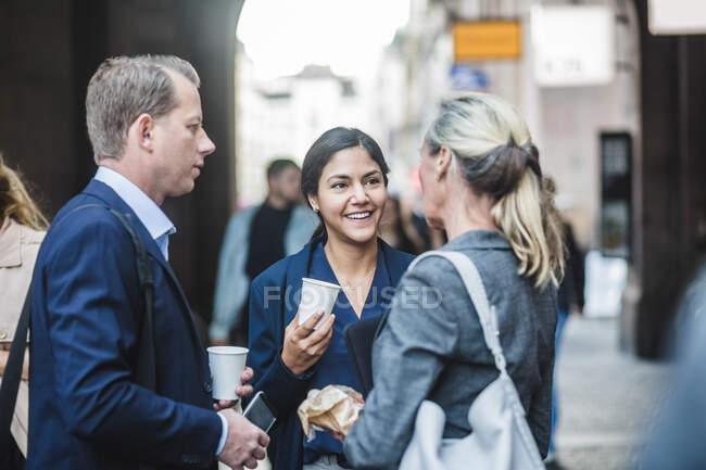 Maturi uomini d'affari in piedi con il collega sorridente in città — Foto stock