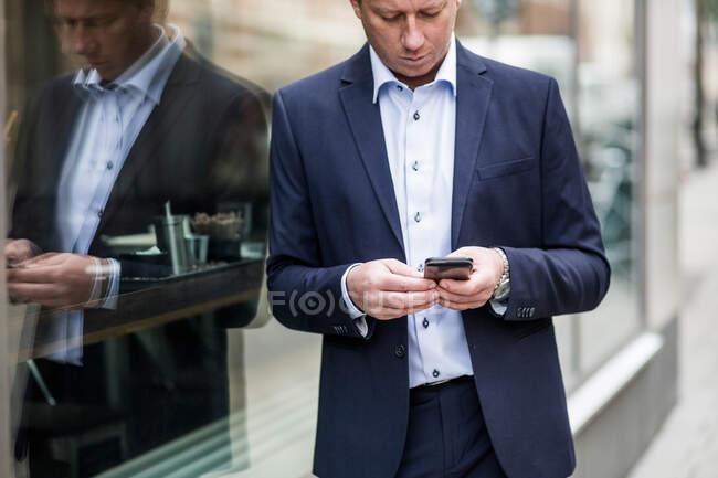 Презренный бизнесмен пользуется смартфоном, стоя у стеклянного окна — стоковое фото