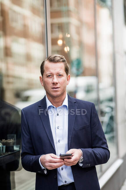 Contemplating mature businessman with smart phone looking away while standing by glass window — Stock Photo