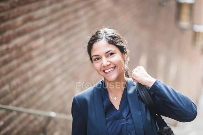Porträt einer Geschäftsfrau mit Tasche, die in der Stadt steht — Stockfoto