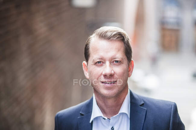 Portrait of smiling mature businessman in city — Stock Photo