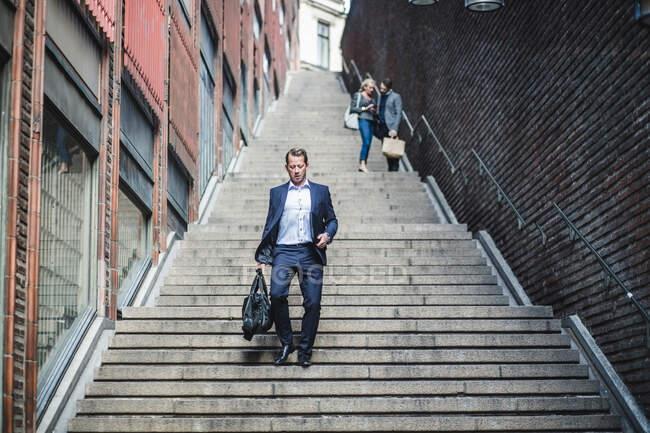 Зрелый мужчина-предприниматель поднимается по лестнице — стоковое фото