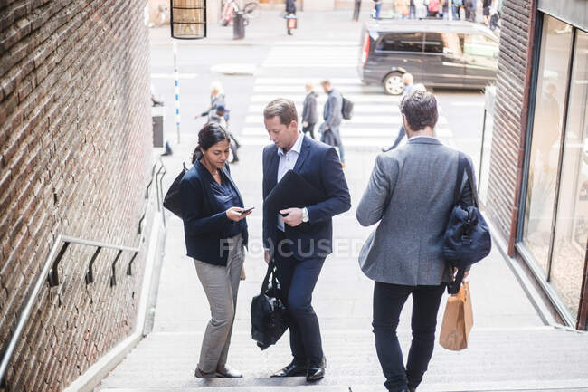 Male and female coworkers using phone on staircase in city — Stock Photo