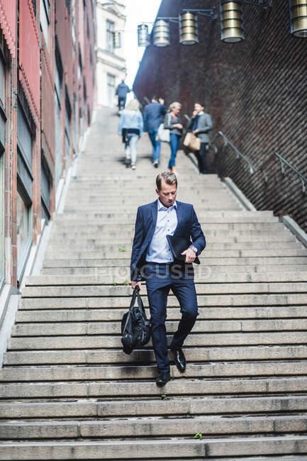 Mature businessman climbing steps — Stock Photo