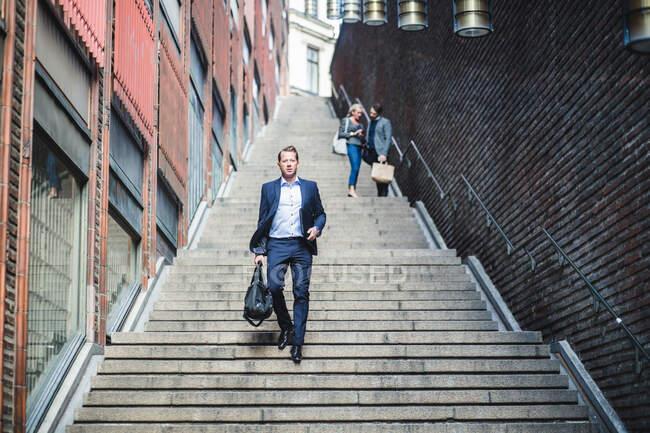 Портрет зрелого бизнесмена, поднимающегося по ступенькам — стоковое фото