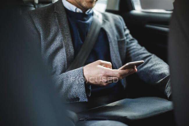 Середина зрелого бизнесмена пользуется телефоном, сидя в машине — стоковое фото