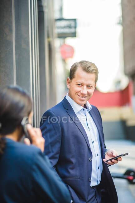 Зрелый бизнесмен со смартфоном смотрит на сослуживца на улице — стоковое фото